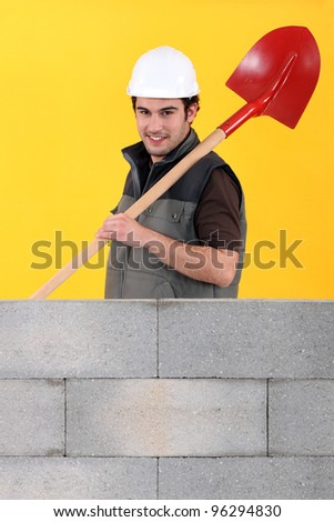 Worker stood by wall with spade