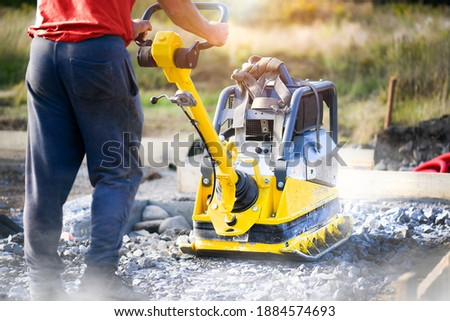 Worker use vibratory plate heavy machine compactor for construction compacting or beating sand at sidewalk. Foto stock ©