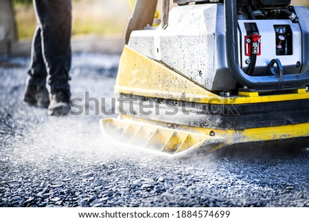 Worker use vibratory plate heavy machine compactor for construction compacting or beating sand at sidewalk. close up or detail photo. Foto stock ©