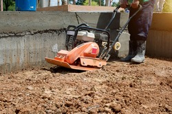 Worker uses compactor to vibratory power tool at soil at worksite construction