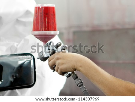 Worker using a red paint spray gun for painting a car