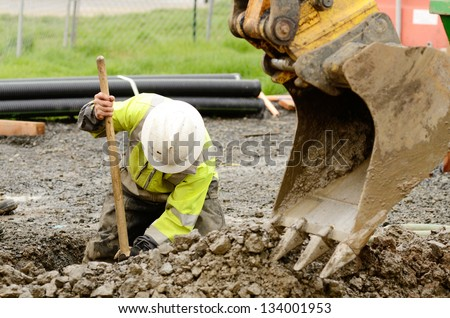Worker using a small tracked excavator to dig a hole to fix a water leak at a large commercial housing development in Oregon stock photo