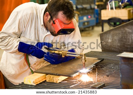 Worker using an acetylene torch to cut through metal in a metalworks factory.