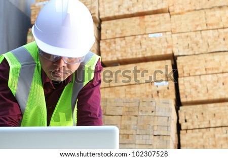 worker using laptop with stacking wood background