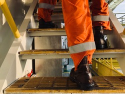 Worker walk with safety shoes on the stairway