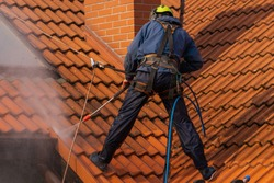 worker washing the roof with pressurized water
