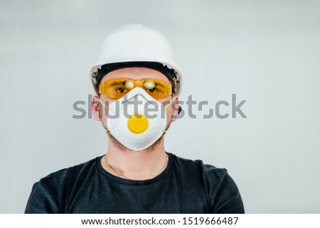 Worker wearing a protective helmet, protective goggles and a protective mask. Work concept, hiring workers for construction. Work on wood, renovation of the flat.