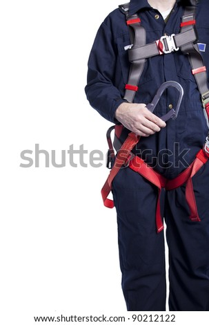 worker wearing blue coveralls and a fall protection harness and lanyard for work at heights