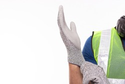 Worker wearing construction safety gloves before working. Caucasian contractor or engineer guy preparing for work at worksite by wear safety glove for protect labor hands copy space, isolated on white