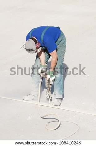 Worker wearing ear and breathing protection using a handheld hydraulic hammer