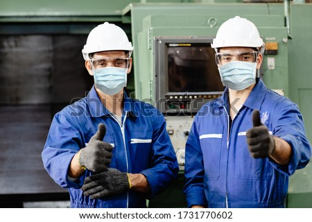 Worker wearing face shield or disposable face mask during working service in factory to prevent Coronavirus(Covid-19) or Air dust pollution in factory.