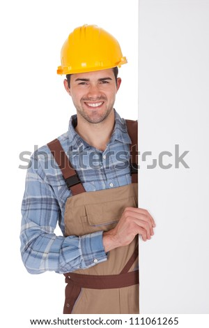 Worker wearing hard hat and holding empty banner. Isolated on white