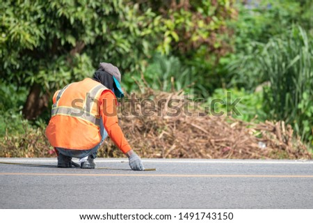 Worker wearing orange uniform is striping with measuring on the road #1491743150