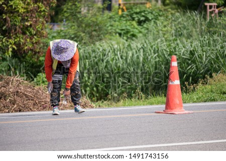 Worker wearing orange uniform is striping with measuring on the road #1491743156