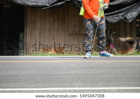 Worker wearing orange uniform is striping with measuring on the road #1495047308