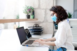 Worker wearing protective mask in safe office. Protection employees on workplace at hotel reception. Young woman working as receptionist. Social distance during covid quarantine, staff safety.