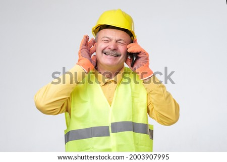 Worker wearing safety helmets close his other ears while talking on mobile phone ストックフォト ©