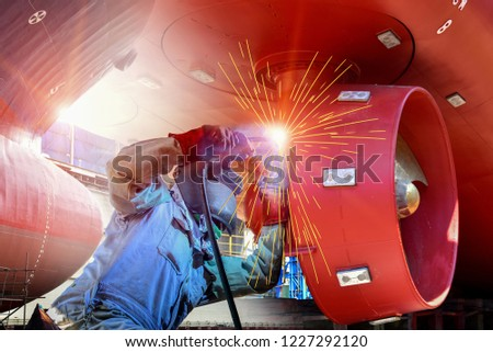 Photo of  Worker Welding process with Metal steel hull and Proppeler Maintenance, wear equipment protective for safety, a large cargo ship repair in dry dock. shipyard Thailand