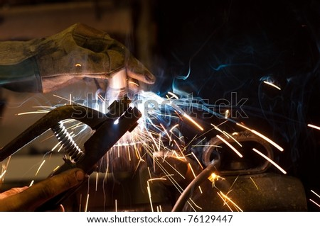 worker welding steel with white sparks