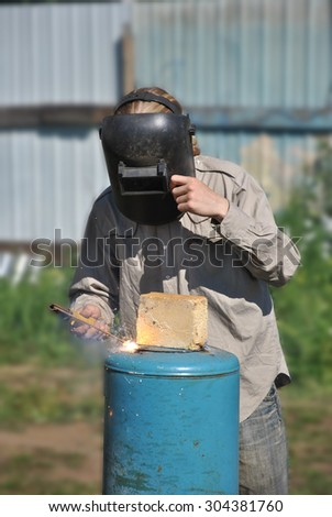 Worker welds in mask blue metal cylinder with electrode outdoor