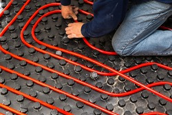Worker who install tubes of radiant underfloor heating installation