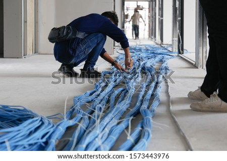 Worker wiring LAN cable at construction site. Unfinished Installation network system. Foto stock ©