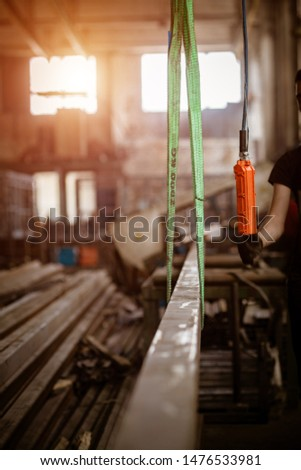Worker with a crane lifts a long metal profile