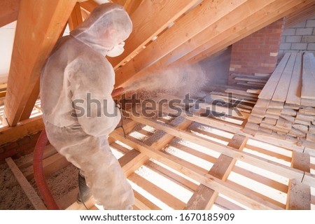 Worker with a hose is strewing ecowool insulation in the attic of a house. Insulation of the attic or floor in the house