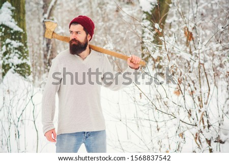 Worker with ax on shoulder in winter snowy forest. Bearded guy chopping tree in woods. Strong man in winter sweater and hat outdoors. Winter lifestyle, fashion Stock photo ©