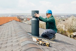 worker with blue helmet on the roof installing iron chimney. roofing Construction and Building New iron House with Modular Chimney.