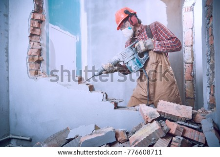 worker with demolition hammer breaking interior wall #776608711
