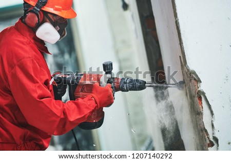 worker with demolition hammer removing plaster or stucco from wall