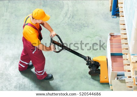 worker with fork pallet truck