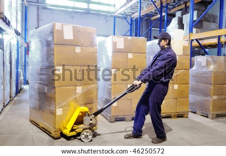 worker with fork pallet truck stacker in warehouse loading Group of cardboard boxes