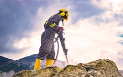 Worker with helmet and protective suit using a drilling machine on top of a large rock