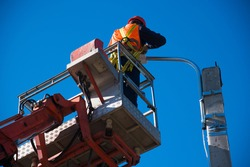 Worker with helmet and safety protective equipment installs new diode lights. Worker in lift bucket repair light pole. Modernization of street lamps.