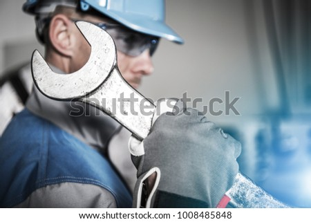 Worker with Huge Iron Wrench Spanner. Heavy Duty Maintenance Concept. Caucasian Technician in Blue Hard Hat.