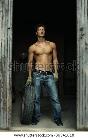 worker with naked torso and a car wheel