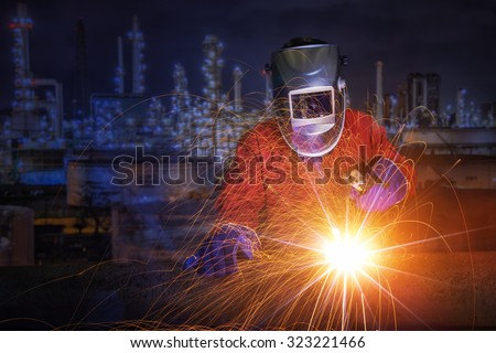 worker with protective mask welding metal and sparks in oil refinary plant.
