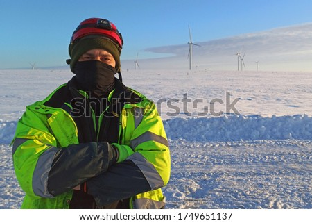 Worker with red helmet and crossed hands in extreme winter cold conditions protected by blazes and face black mask. Snow field with remoted wind turbine on background.