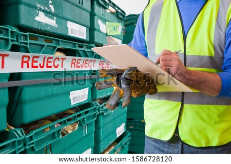 Worker With Rejected Produce In Food Processing Warehouse
