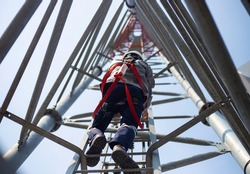 Worker with safety equipment climb high telecom tower for 5G maintenance working