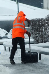 worker with safety vest at snow clearance with a snow shovel in winter