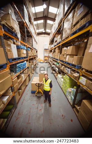 Worker with trolley of boxes in a large warehouse