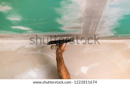 Worker with trowel and / or American trowel apply putty to the gypsum plasterboards with matched flaps