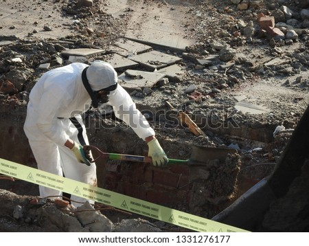 Worker with white protective suit, gloves and mask removes removal white asbestos on construction site. Demolition building, barrier tape  warning, caution hazard. Action picture, part of a serie.