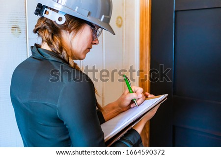 worker woman wears a grey hardhat and protective eyewear at work. female construction inspector taking notes on her clipboard during a home inspection Сток-фото ©
