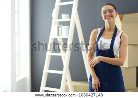 Worker woman with drill standing in new home #1080427148