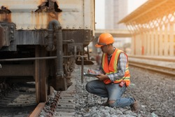 Worker work and check break system of  train .   Engineer man check list wheel System on railways.