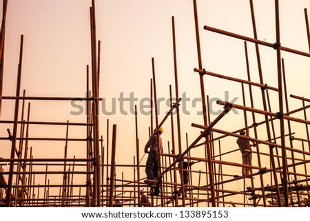 worker working on scaffold near sunset